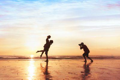 Photographer on a beach with a couple